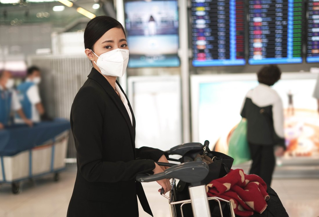Woman wearing a mask at the airport - the future of travel